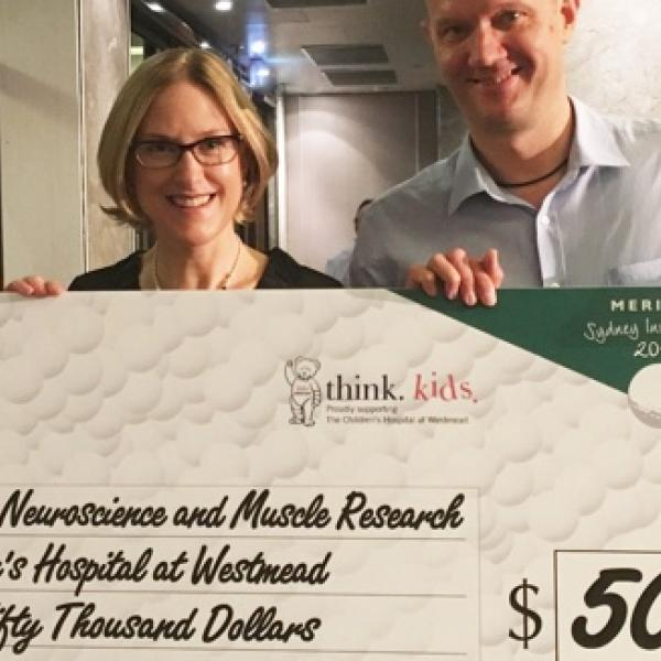 A/Prof Sandra and Prof Russell holding a donation card from Meriton
