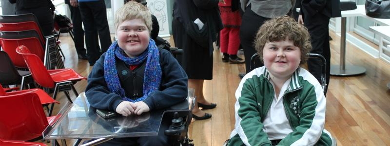 Photo of two children. One is sitting on a wheelchair